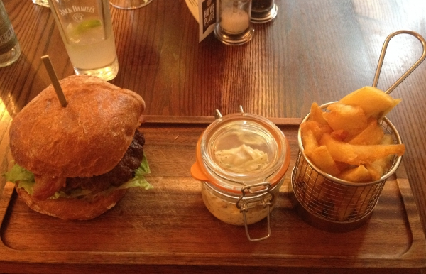 A well lit photo of the burger and fat chips from Hove Place on a wooden board